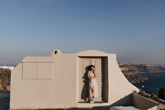 Jonge aantrekkelijke vrouw in midi-jurk poseert in de buurt van beige huis