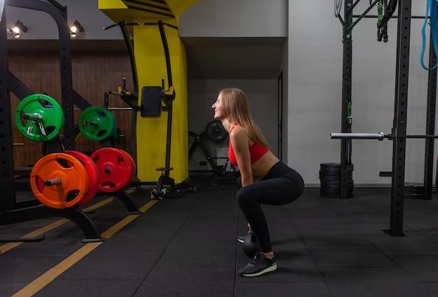 Jonge aantrekkelijke vrouw in sportkleding beoefent zware kettlebell-oefening in moderne sportschool. vrije gewichten training