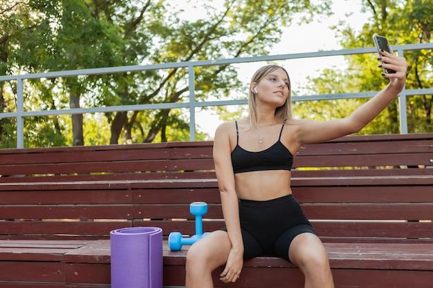 Jonge aantrekkelijke vrouw in sportkleding die rust terwijl ze op houten stands zit na een ochtendtraining in de buitenlucht en selfie op smartphone doet