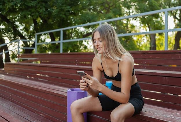Jonge aantrekkelijke vrouw in sportkleding die rust terwijl ze op houten stands zit na een zware ochtendtraining in de buitenlucht en smartphone gebruikt