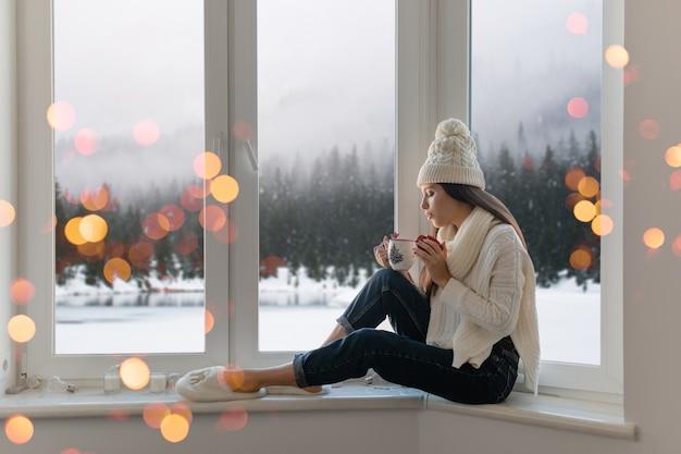 Jonge aantrekkelijke vrouw in stijlvolle witte gebreide trui, sjaal en muts om thuis te zitten op de vensterbank met kerstmis kopje warme thee drinken, winter bos achtergrond weergave, lichten bokeh houden