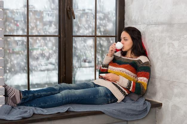 Jonge aantrekkelijke vrouw in warme gebreide trui die op de kussens op de vensterbank ligt en een kopje koffie drinkt terwijl het sneeuwt