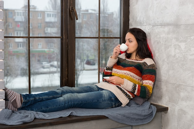 Jonge aantrekkelijke vrouw in warme gebreide trui die op de kussens op de vensterbank ligt en een kopje koffie drinkt