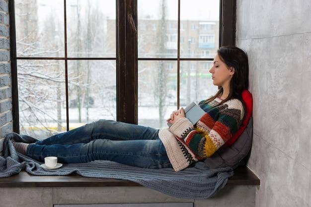 Jonge aantrekkelijke vrouw in warme gebreide trui valt in slaap op de vensterbank met kussens tijdens het lezen van een boek