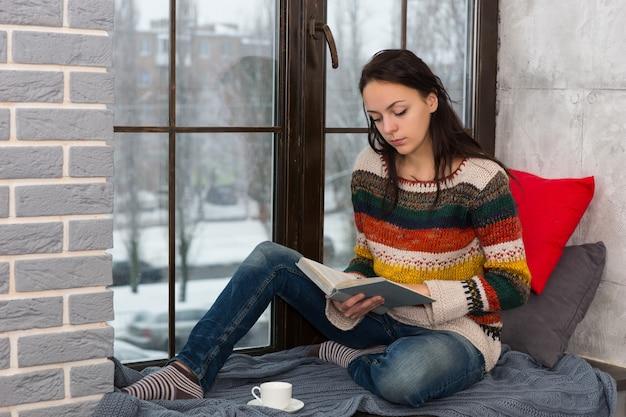 Jonge aantrekkelijke vrouw in warme gebreide trui zittend op de vensterbank met kussens en deken en een boek lezen