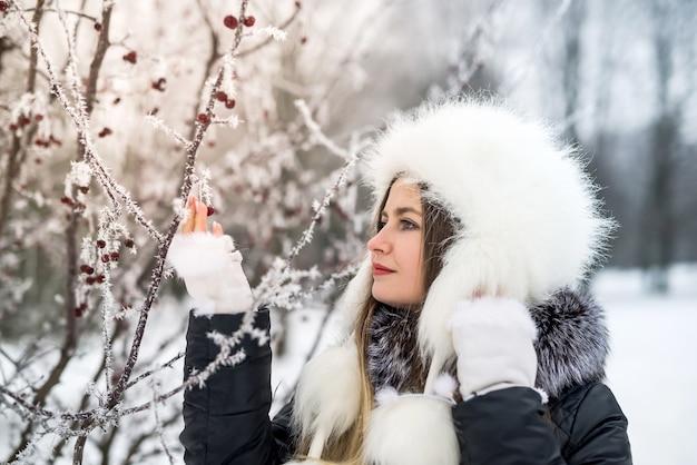 Jonge aantrekkelijke vrouw in winter park met takken