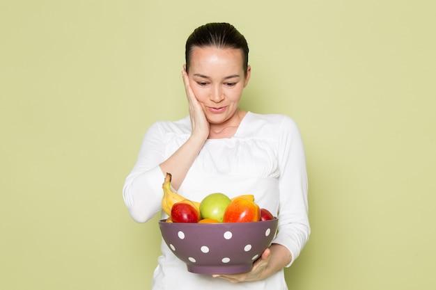 Jonge aantrekkelijke vrouw in wit overhemd dat en fruitkom glimlacht toont
