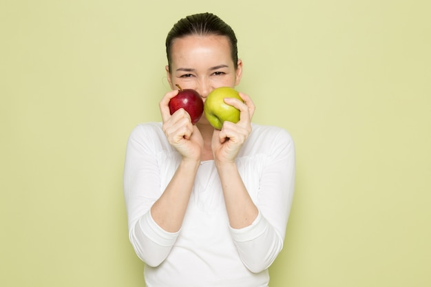 Jonge aantrekkelijke vrouw in wit overhemd dat en groene en rode appelen glimlacht houdt