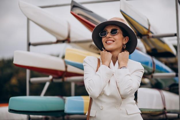 Jonge aantrekkelijke vrouw in witte jas buiten wandelen