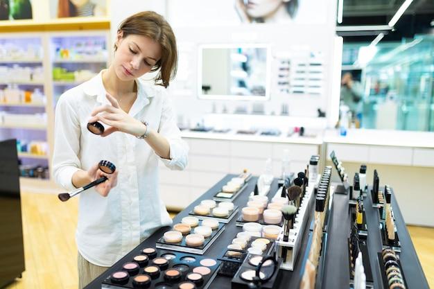 Jonge aantrekkelijke vrouw kiest kleur van poeder op make-up hoek