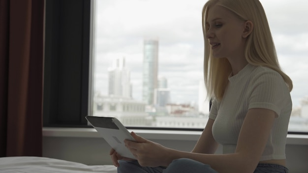 Jonge aantrekkelijke vrouw maakt videogesprekken in de slaapkamer met een groot raam. een gelukkige vrouw toont op de video een prachtig uitzicht vanuit het raam van de metropool. 4k uhd