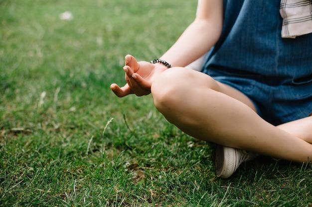 Jonge aantrekkelijke vrouw mediteren in park.