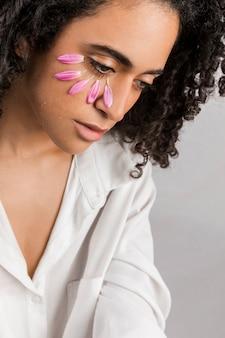 Jonge aantrekkelijke vrouw met bloemblaadjes op gezicht huilen
