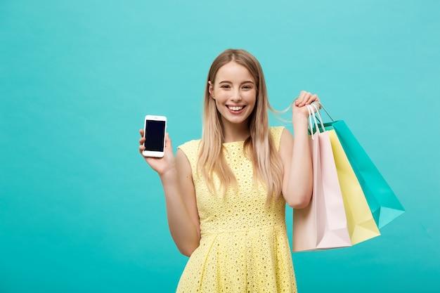 Jonge aantrekkelijke vrouw met boodschappentassen toont het scherm van de telefoon rechtstreeks naar de camera.