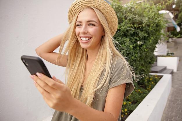 Jonge aantrekkelijke vrouw met charmante glimlach proberen te maken van selfie met mobiele telefoon, haar strooien hoed met hand rechttrekken, in een goede bui