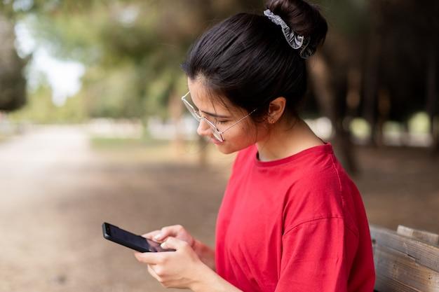 Jonge aantrekkelijke vrouw met een bril zitten in een bankje en met behulp van haar telefoon in een park, met een rood shirt. sevilla, spanje