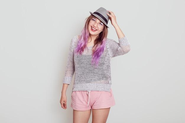 Jonge aantrekkelijke vrouw met een vrolijke gezichtsuitdrukking die direct naar de camera kijkt met een brede glimlach, haar hoed aanraakt, in een goed humeur is, geïsoleerd over een grijze achtergrond.