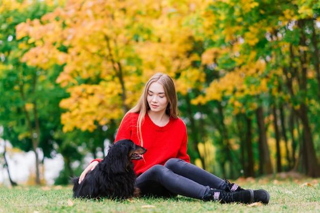 Jonge aantrekkelijke vrouw met haar teckel hond in haar armen buiten in zonsopgang park in de herfst tijd