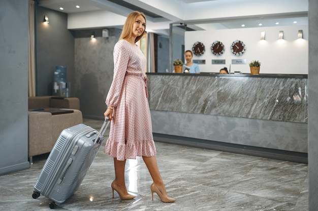 Jonge aantrekkelijke vrouw met ingepakte koffer die zich in hotellobby bevindt