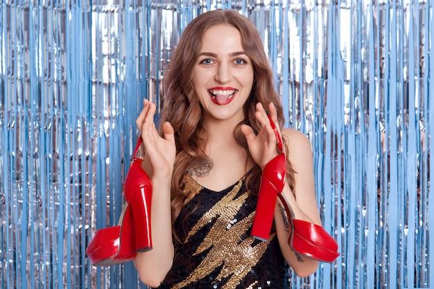 Jonge aantrekkelijke vrouw met lichte make-up, poseren tegen blauwe muur met decor regen en rode schoenen met hoge hakken te houden