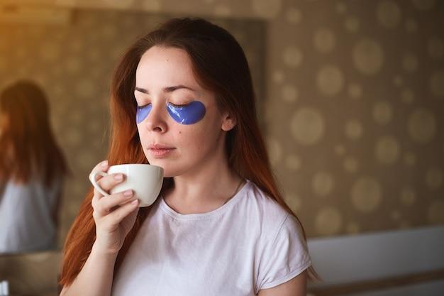 Jonge aantrekkelijke vrouw met masker onder ogen die koffie drinken. mooie vrouw met natuurlijke make-up, hebben collageenvlekken op de frisse gezichtshuid in huis. ochtend routine