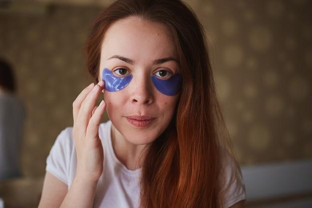 Jonge aantrekkelijke vrouw met masker onder ogen. mooie vrouw met natuurlijke make-up, hebben collageenvlekken op de frisse gezichtshuid in huis. ochtend routine