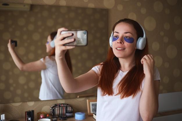 Jonge aantrekkelijke vrouw met masker onder ogen selfie maken. mooie vrouw met natuurlijke make-up, hebben collageenvlekken op de frisse gezichtshuid in huis. ochtend routine