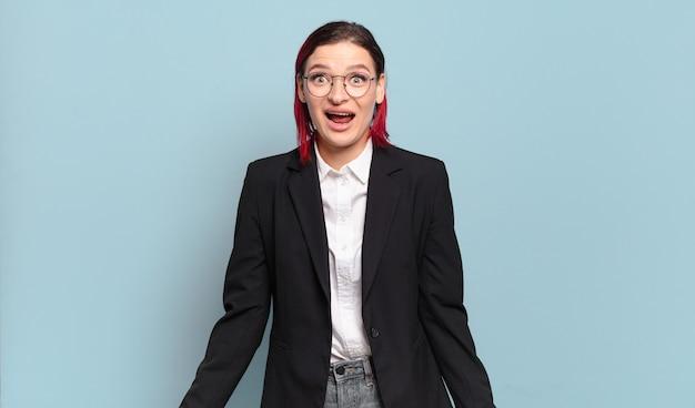 Jonge aantrekkelijke vrouw met rood haar die er blij en aangenaam verrast uitziet, opgewonden met een gefascineerde en geschokte uitdrukking