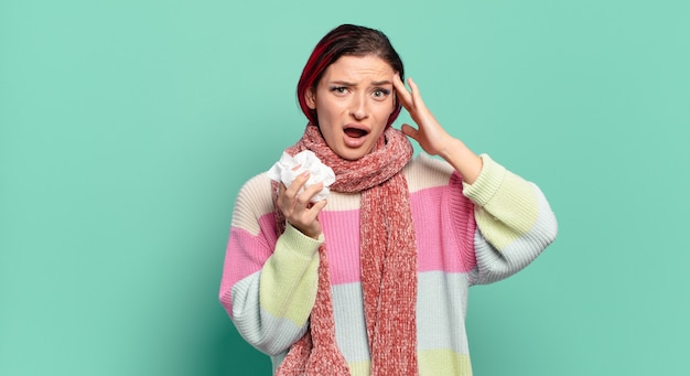 Jonge aantrekkelijke vrouw met rood haar die er blij, verbaasd en verrast uitziet, lacht en een verbazingwekkend en ongelooflijk goed nieuws griepconcept realiseert