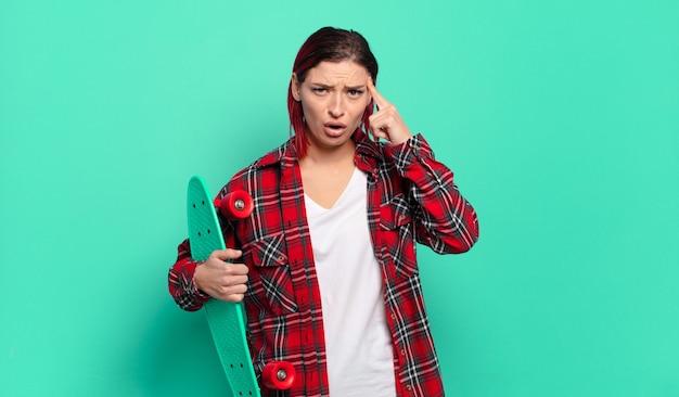 Jonge aantrekkelijke vrouw met rood haar die verrast, met open mond, geschokt kijkt, een nieuwe gedachte, idee of concept realiseert en een skatebord vasthoudt