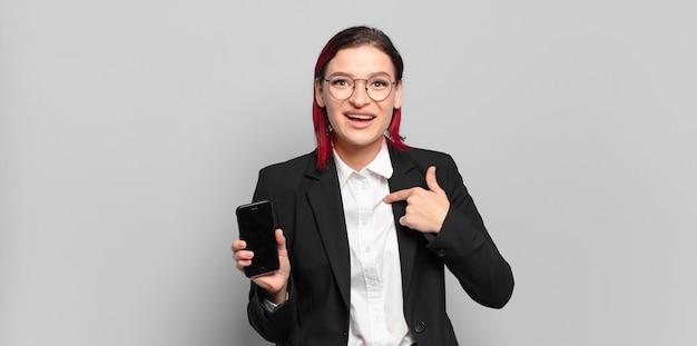 Jonge aantrekkelijke vrouw met rood haar die zich blij, verrast en trots voelt en naar zichzelf wijst met een opgewonden, verbaasde blik