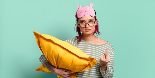 Jonge aantrekkelijke vrouw met rood haar die zich boos, geïrriteerd, opstandig en agressief voelt, de middelvinger omdraait, terugvecht en pyjama draagt.