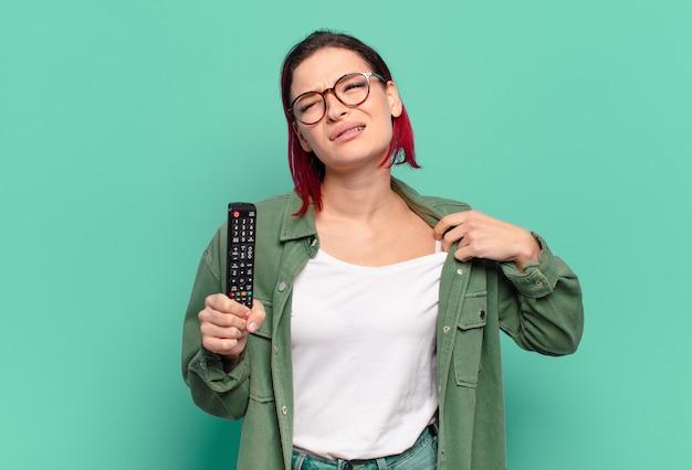 Jonge aantrekkelijke vrouw met rood haar die zich gestrest, angstig, moe en gefrustreerd voelt en de hals van het shirt trekt