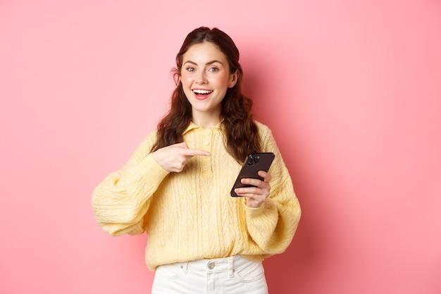 Jonge aantrekkelijke vrouw met smartphone, wijzend op het scherm, promoot, praat over haar social media-pagina, staande over de roze muur.