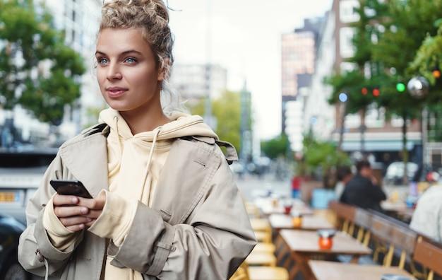 Jonge aantrekkelijke vrouw met smartphoneapplicatie, wegkijken naar auto's op straat.