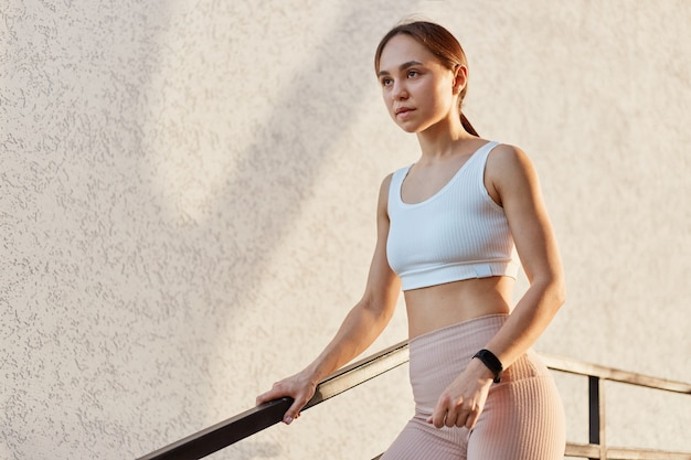 Jonge aantrekkelijke vrouw met witte top en leggins die bij de trapleuning staan en wegkijken