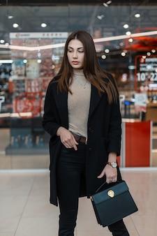 Jonge aantrekkelijke vrouw model met lang haar in zwarte jas in jeans met modieuze lederen handtas staat in een winkelcentrum. stijlvolle schattig meisje mannequin in de winkel. casual stijl. trendy kleding voor vrouwen