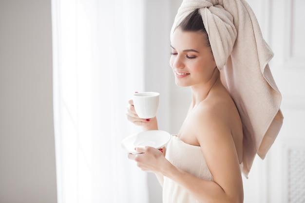 Jonge aantrekkelijke vrouw na het baden in de ochtend