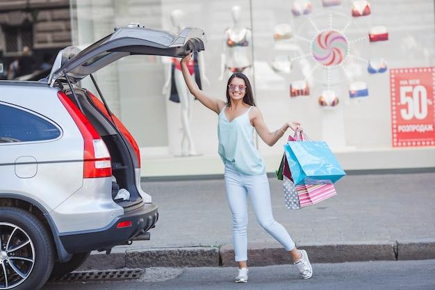 Jonge aantrekkelijke vrouw na het winkelen. vrouw zetten haar boodschappentassen in de auto. vrolijke dame bij winkelcentrum.