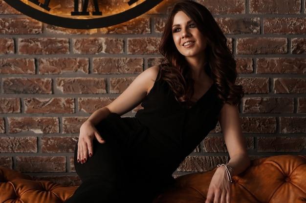 Jonge aantrekkelijke vrouw onder de klok, op bakstenen muur