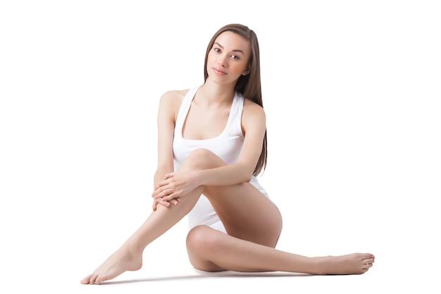 Jonge aantrekkelijke vrouw op witte geïsoleerde muur volle lengte. lichaamsverzorging concept.
