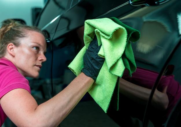 Jonge aantrekkelijke vrouw polijsten carrosserie in dienst