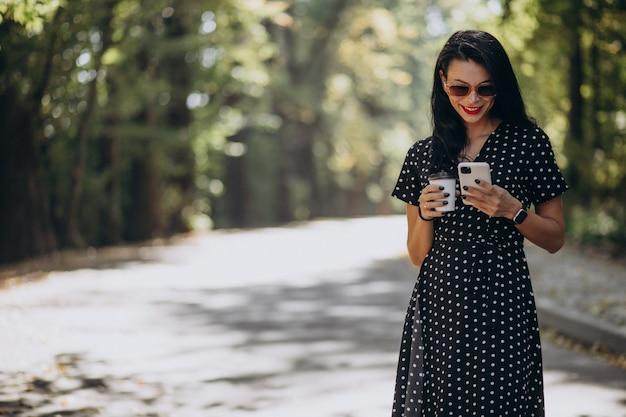 Jonge aantrekkelijke vrouw praten over de telefoon in park