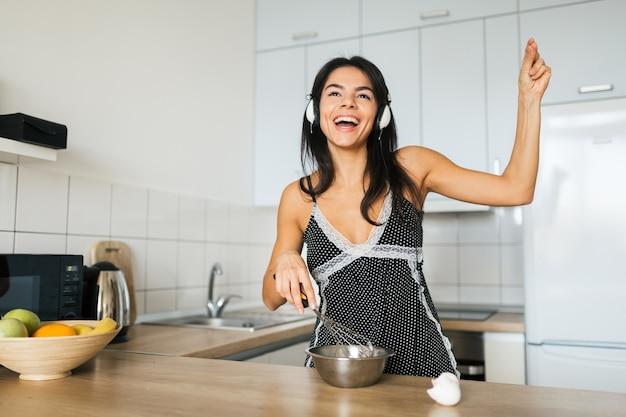 Jonge aantrekkelijke vrouw roerei koken in de keuken in de ochtend, glimlachen, gelukkig positieve huisvrouw, gezonde levensstijl, luisteren naar muziek op de koptelefoon, lachen, plezier maken, dansen, zingen