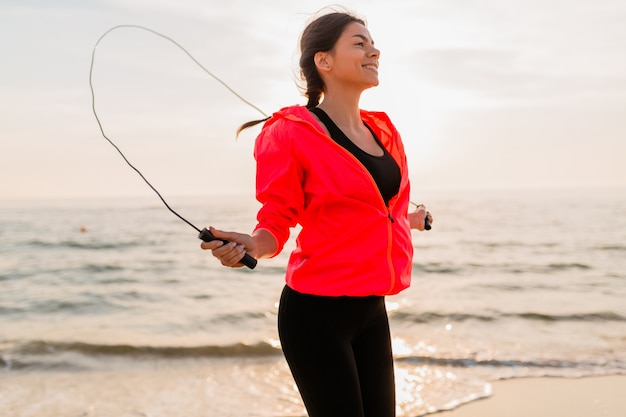 Jonge aantrekkelijke vrouw sport oefeningen in ochtend zonsopgang op zee strand in sportkleding, gezonde levensstijl, luisteren naar muziek op oortelefoons, roze windjack dragen, springen in springtouw