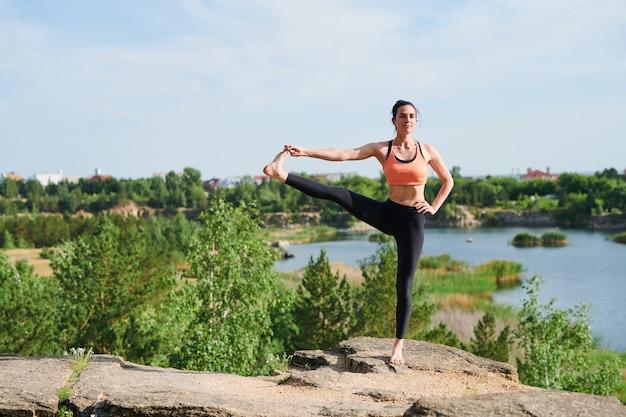 Jonge aantrekkelijke vrouw staande evenwicht pose tijdens het doen van utthita hasta padangusthasana bij steengroeve