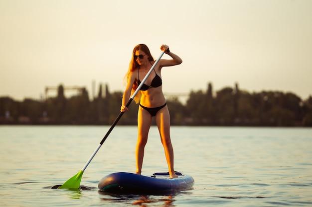 Jonge aantrekkelijke vrouw staande op paddle board, sup. actief leven, sport, vrijetijdsbesteding concept