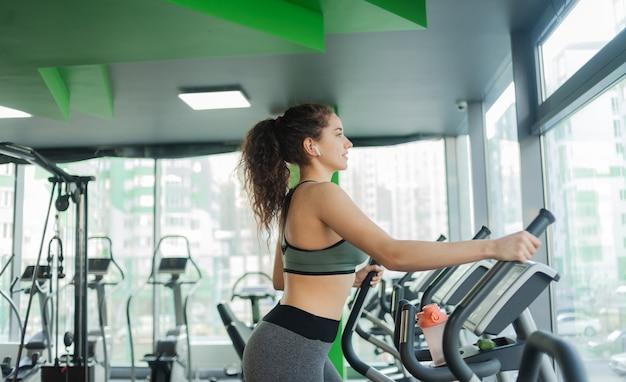 Jonge aantrekkelijke vrouw warming-up op een elliptische oefening machine in de sportschool. fitness, gezonde levensstijl concept.