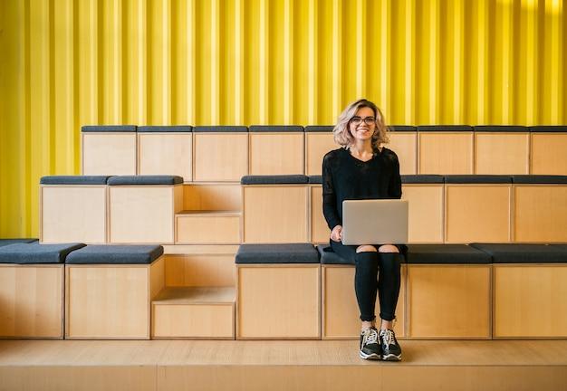 Jonge aantrekkelijke vrouw zitten in de collegezaal, die op laptop werkt, een bril draagt, een modern auditorium, online studentenstudie, freelancer, glimlachen, tieneropstarten