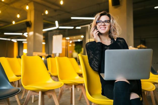 Jonge aantrekkelijke vrouw zitten in de collegezaal, die op laptop werkt, een bril draagt, veel gele stoelen, online studentenstudie, freelancer, glimlachen, praten op smartphone, vooruit kijken, opstarten